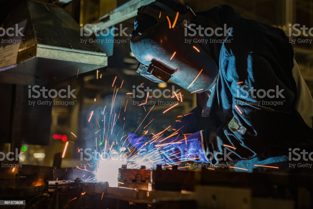 Industrial worker is welding assembly part in car factory stock photo
