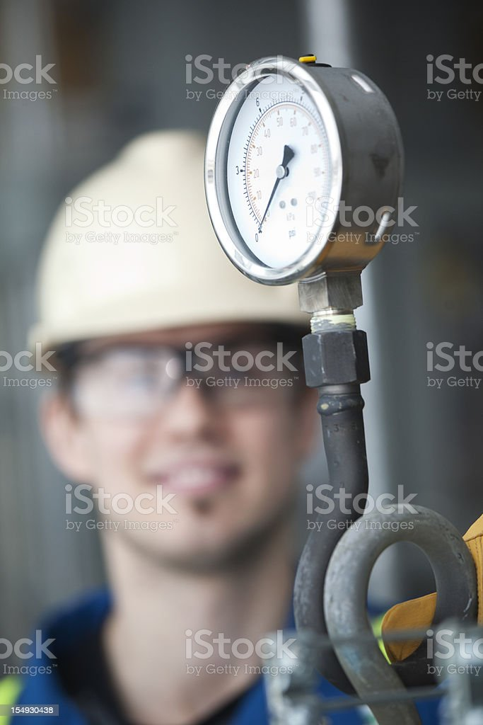 Industrial Worker looking at gauge stock photo