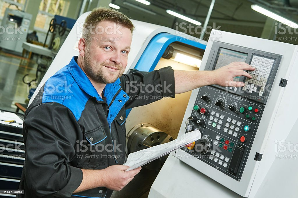 industrial worker operating cnc turning machine in metal machining industry stock photo