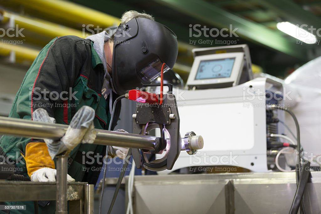 Industrial worker setting orbital welding machine. stock photo