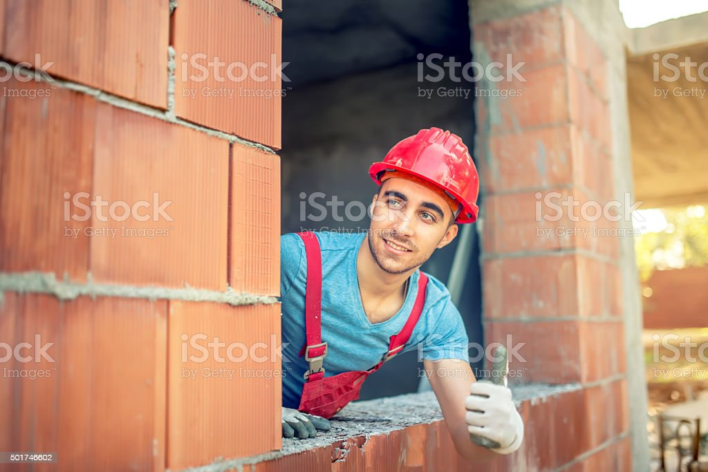industrial worker showing ok hand sign on construction site stock photo