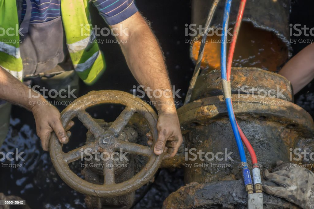 Industrial worker turning a valve on a large pipe 2 stock photo