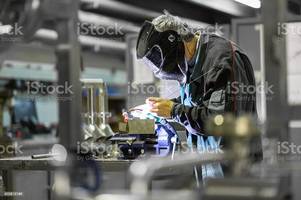 Industrial worker welding in metal factory. stock photo