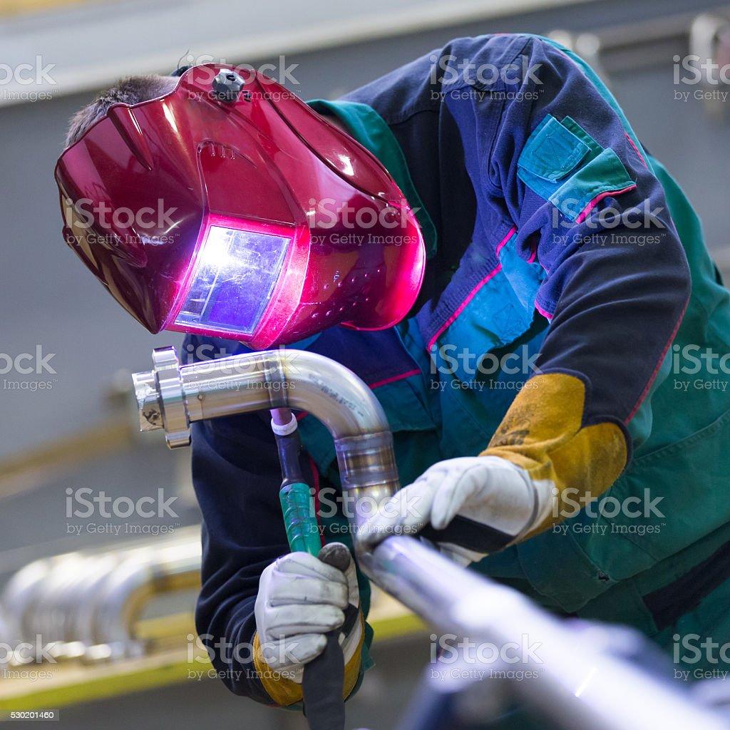 Industrial worker welding in metal factory. stock photo