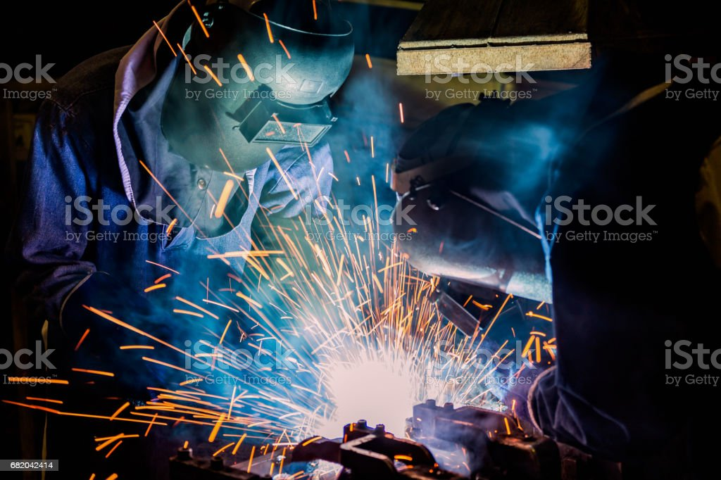 Industrial workers are welding assembly metal part in factory stock photo