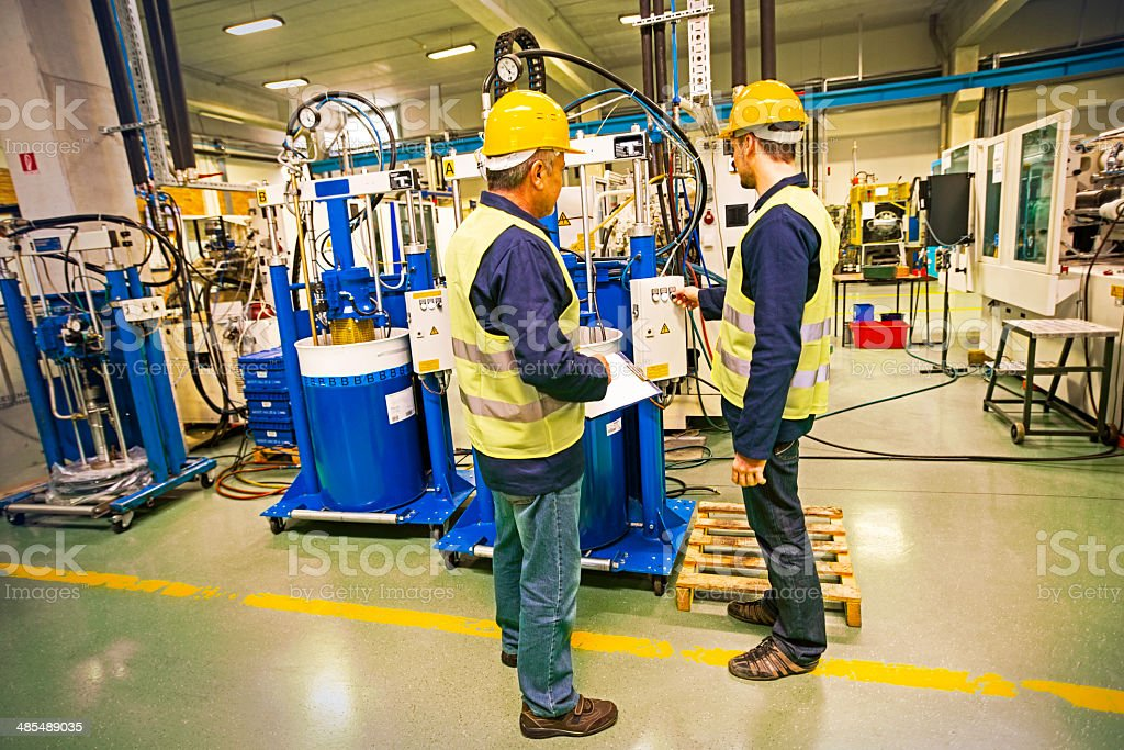 Industrial Workers Control New Machine in the Factory stock photo