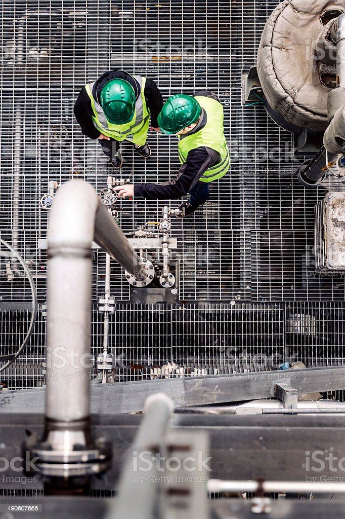 Industrial workers discussing by pipeline stock photo