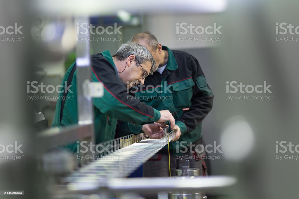 Industrial workers in manufacturing plant. stock photo