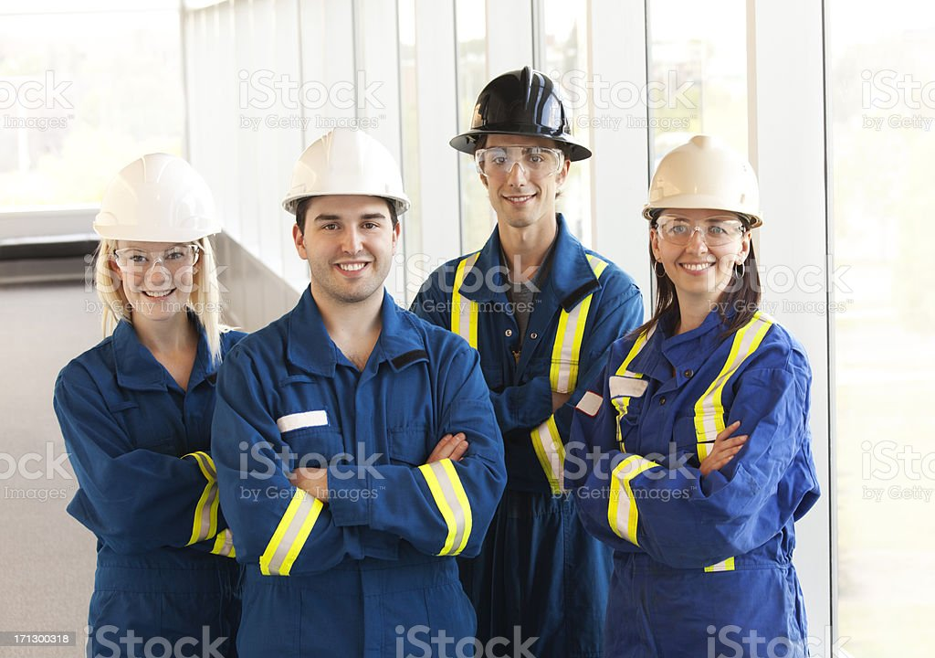 Industrial workers with arms crossed wearing hard hats stock photo