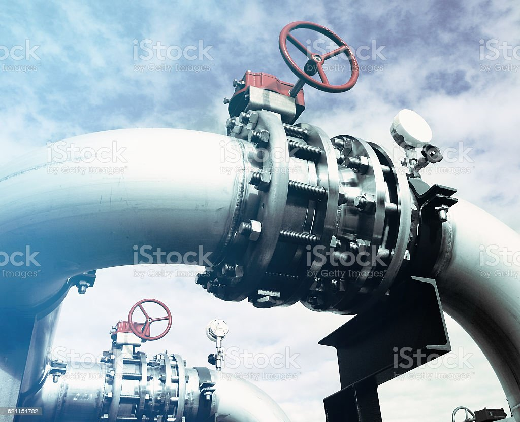 Industrial zone, Steel pipelines and valves against blue sky stock photo