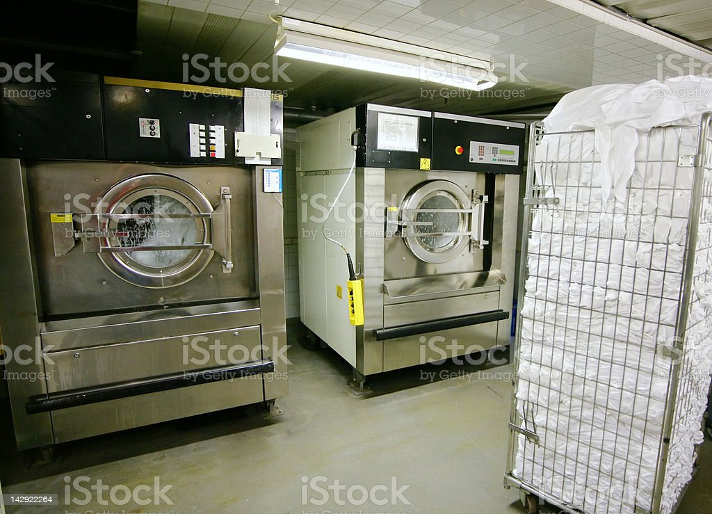 Industrial-sized washer and dryer with pile of white towels stock photo