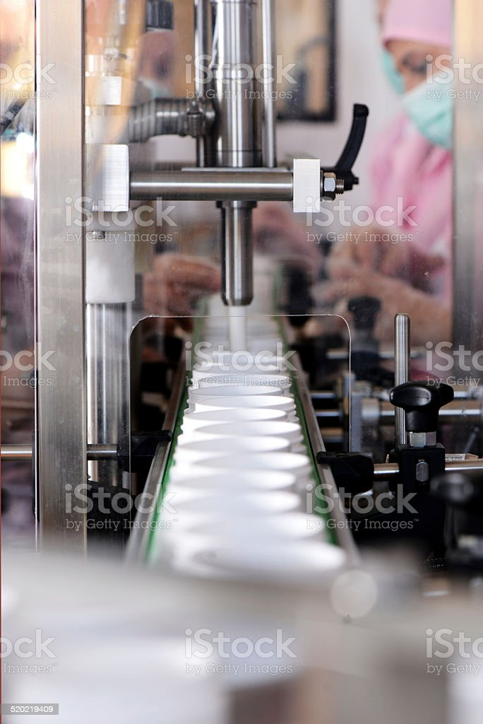 industry machine is filling cream in the boxes stock photo
