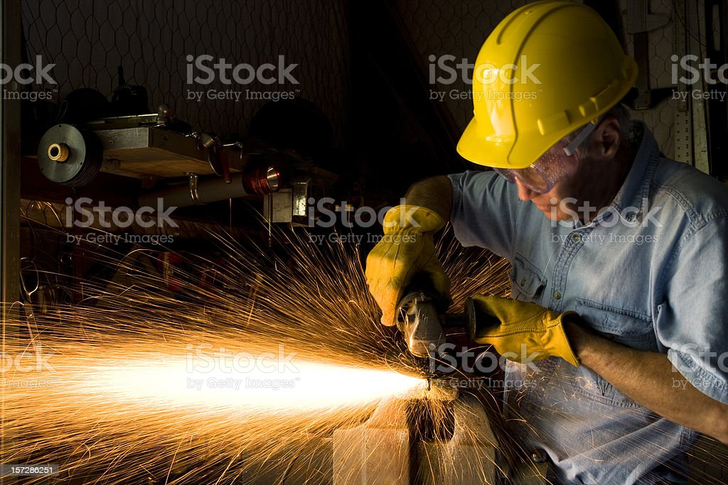 Industry: Man Grinding in workshop wearing hardhat and gloves.  Sparks stock photo