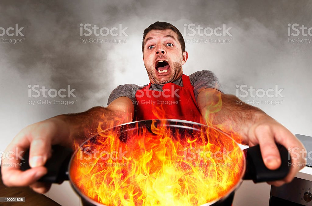 inexperienced home cook holding pot burning fire in panic stress stock photo