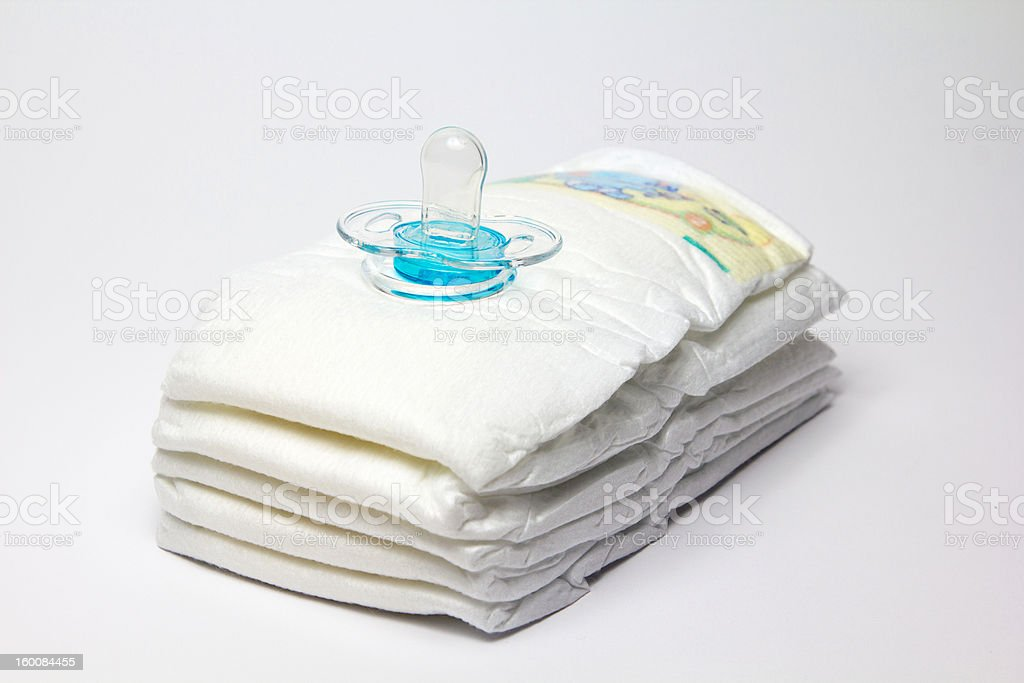 Infant diapers and clear blue pacifier royalty-free stock photo