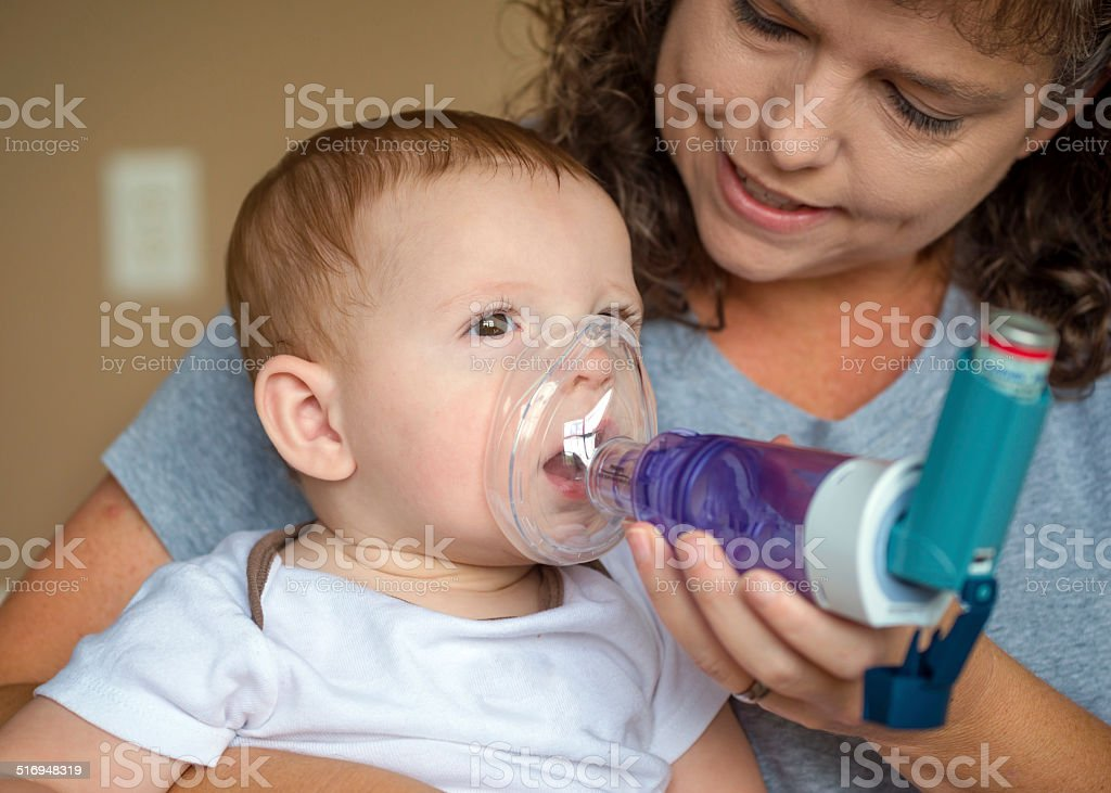Infant getting breathing treatment from mother stock photo