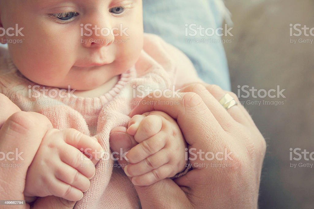 Infant Girl Holding Fathers Hands stock photo