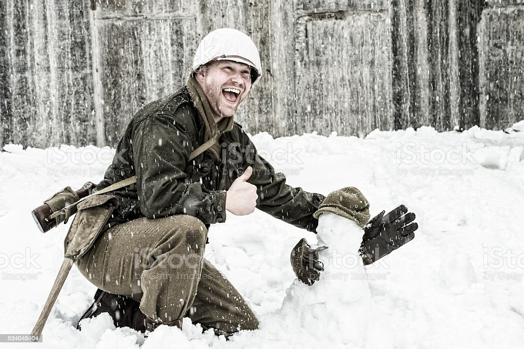 WWII US Infantry Man Building A Snowman and Laughing stock photo