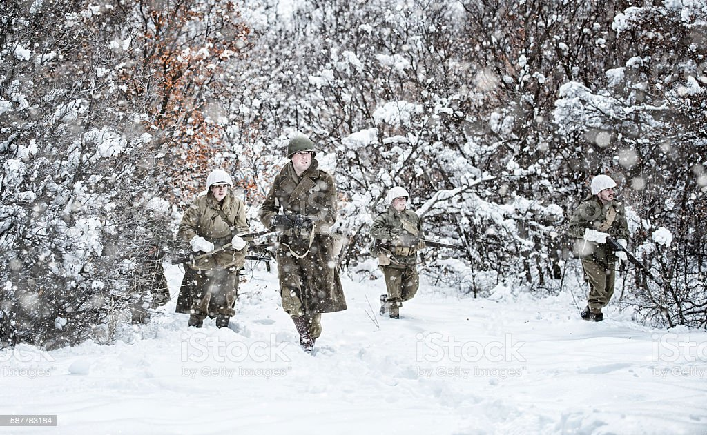 WWII US Infantry On Patrol In A Snowy Rural Area stock photo