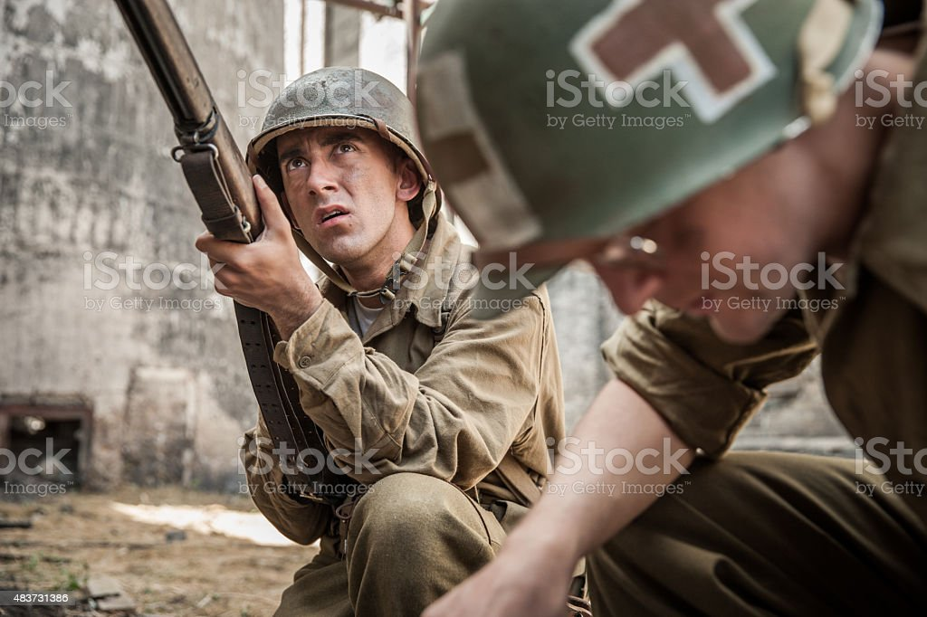 WWII Infantry Soldier Guards Medic Administering First Aid to Fa stock photo