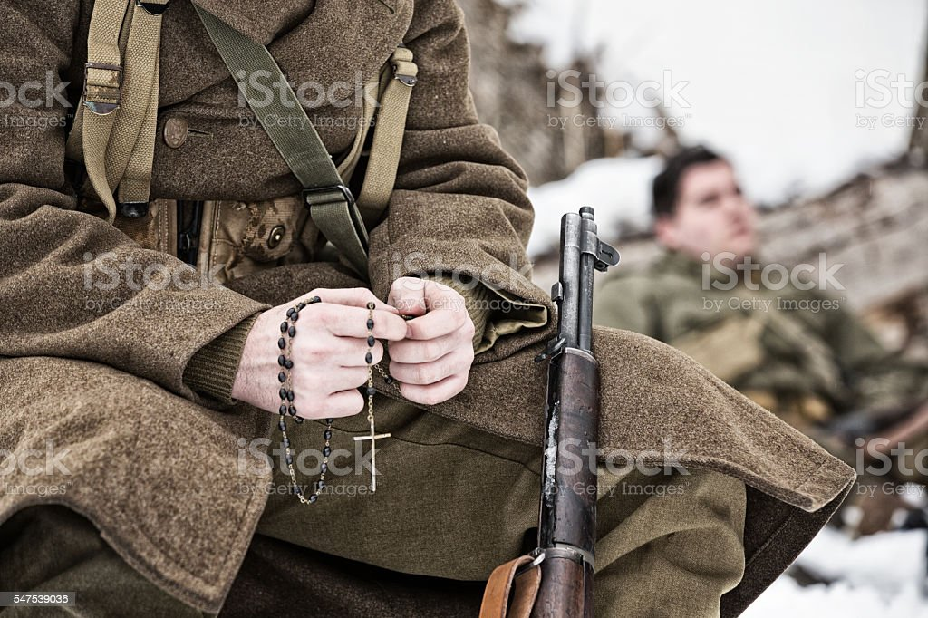 WWII Infantry Soldier Sitting in the Snow Praying the Rosary stock photo