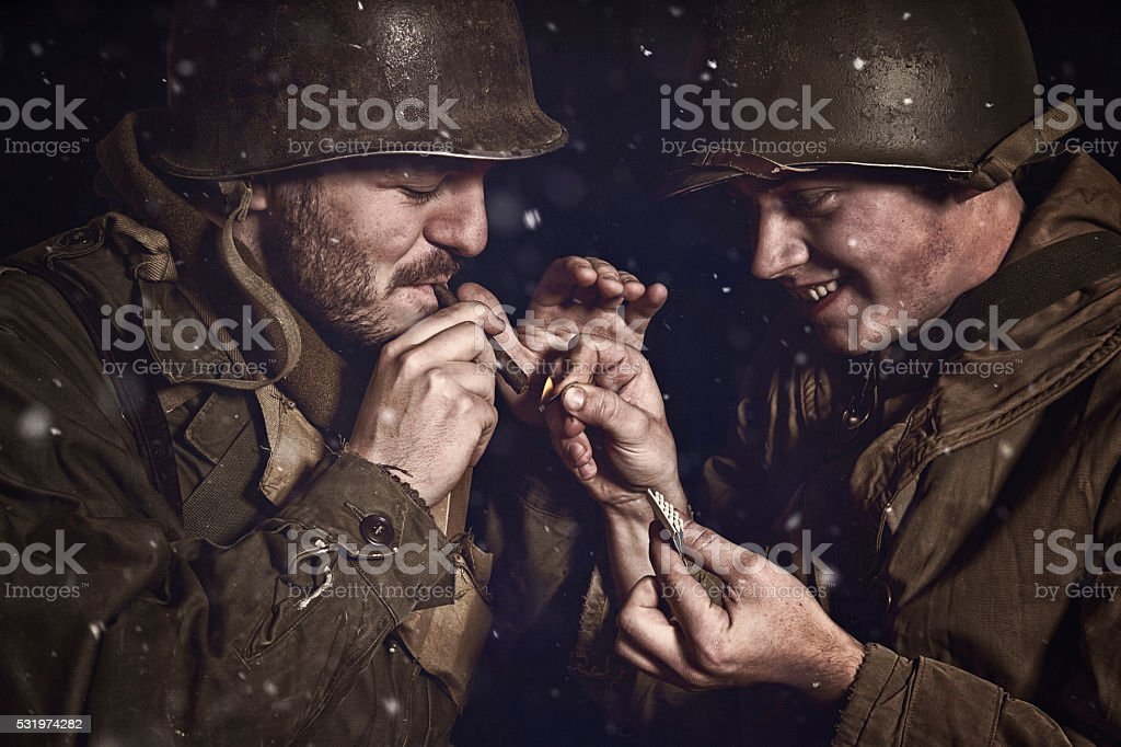 WWII US Infantry Soldiers Lighting A Cigar At Night stock photo