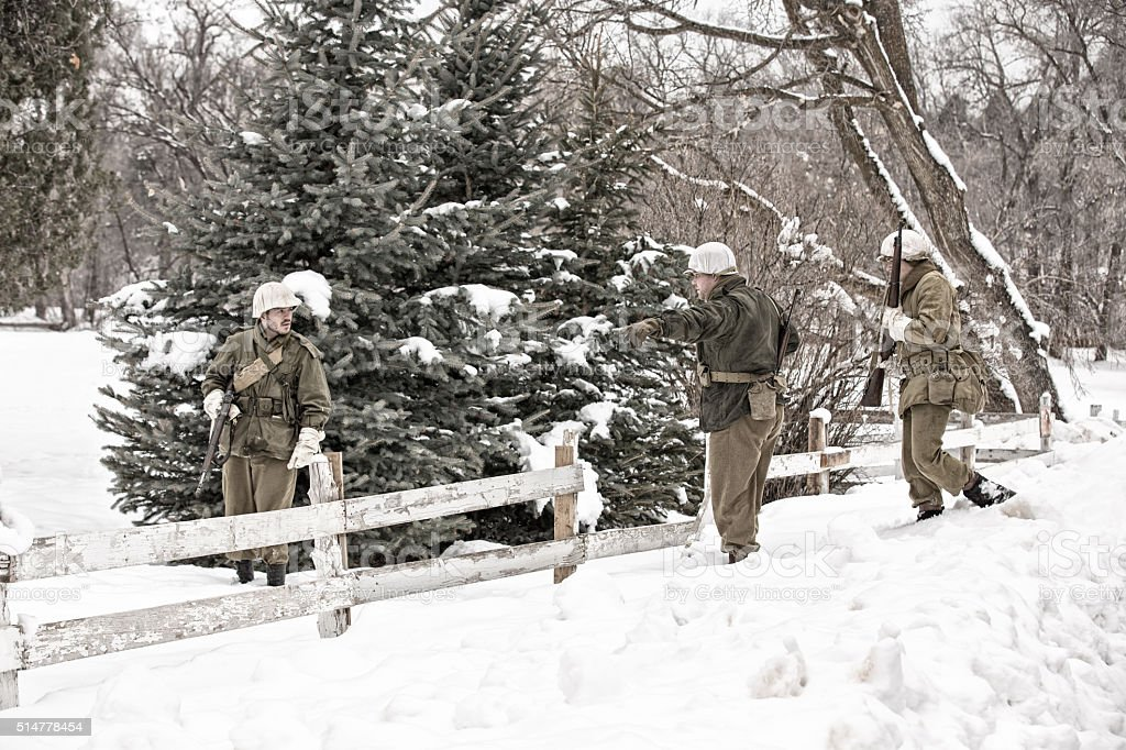 WWII US Infantry Soldiers Patrolling Winter Countryside stock photo