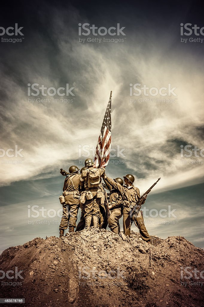 WWII Infantry Squad Hoists Flag on Hill stock photo