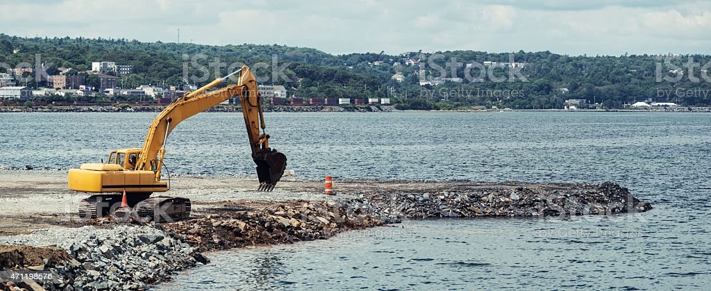 Infilling Harbourfront with Excavator stock photo