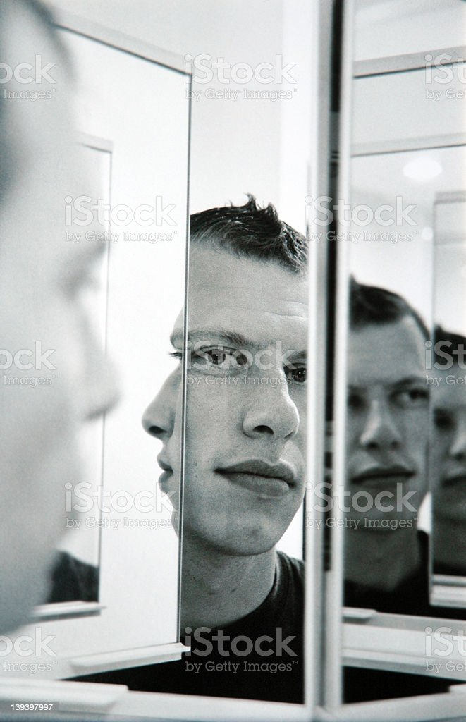 Infinite faces of a young man's reflection in a mirror stock photo