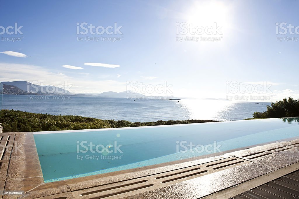 Infinity pool with a large lake in the background stock photo