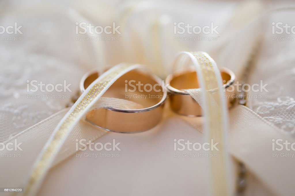 infinity sign of the rings, wedding rings on a white background,wedding bands, wedding rings on a cushion stock photo