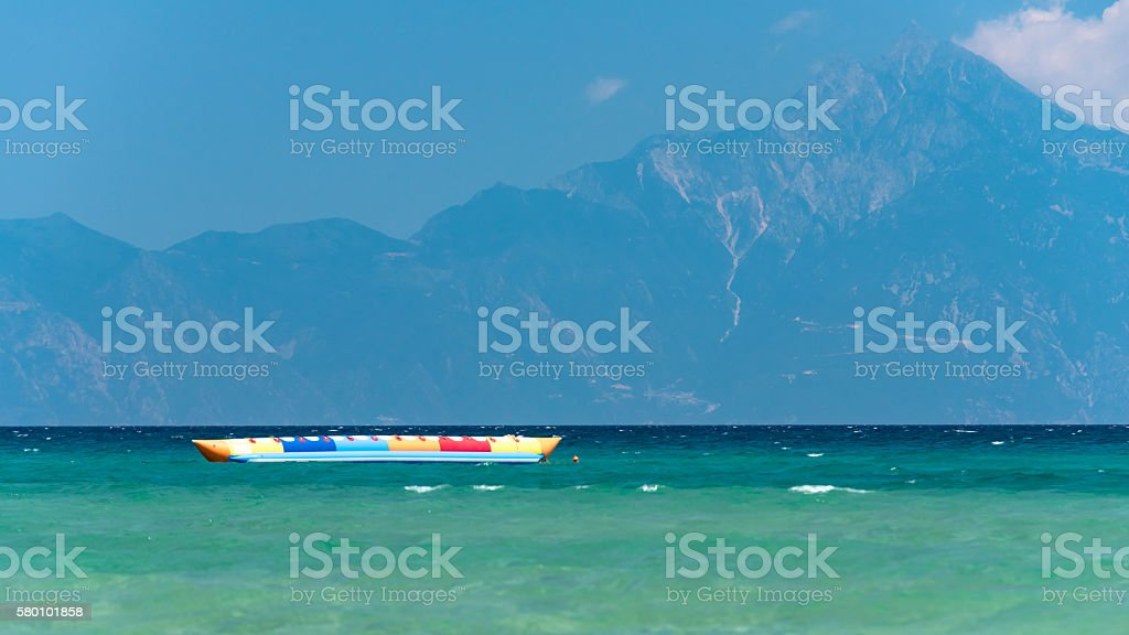 Inflatable banana shaped boat at sunset on a calm sea, stock photo