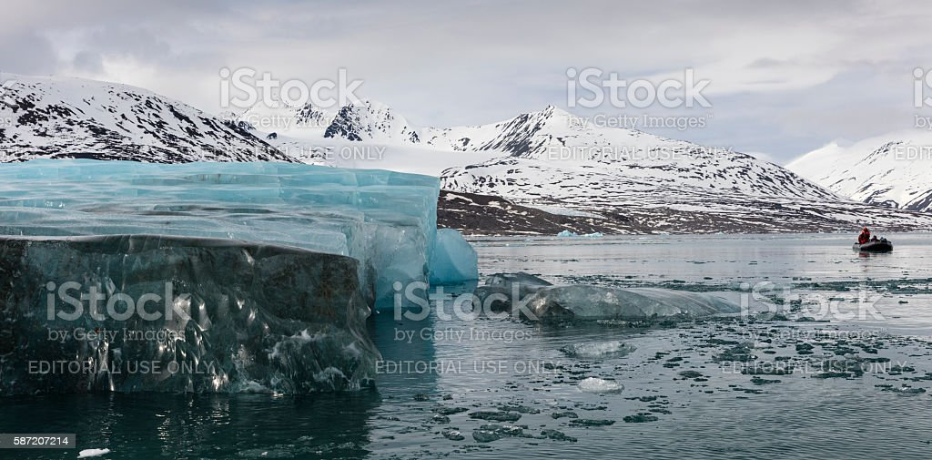 Inflatable boat cruising amid icebergs in Leifdefjorden, Svalbard, Norwegian Arctic stock photo