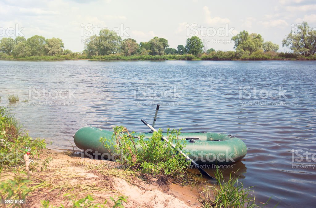 Inflatable boat on the a river near shore stock photo