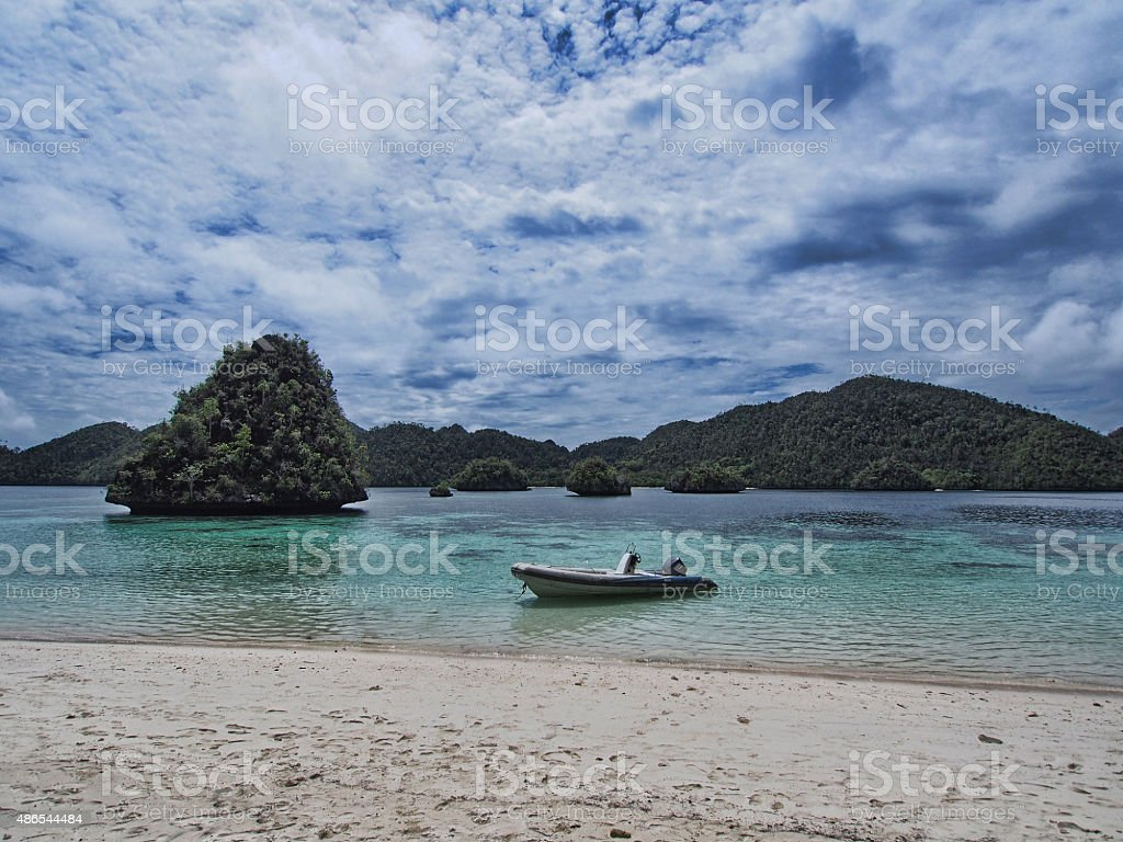 Inflatable Raft floating next to white sand beach stock photo
