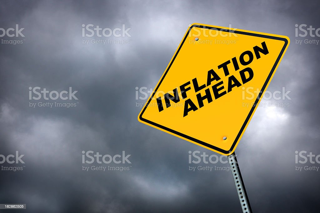 Inflation ahead road sign in front of cloudy sky background stock photo