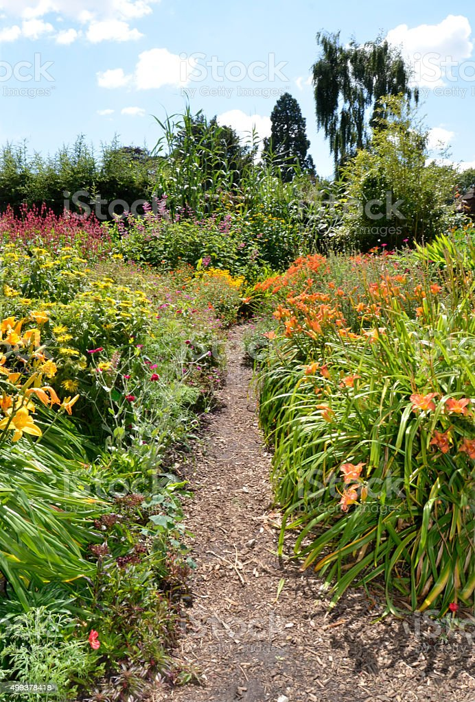 Informal Country Garden Footpath Between Colourful Flowers stock photo