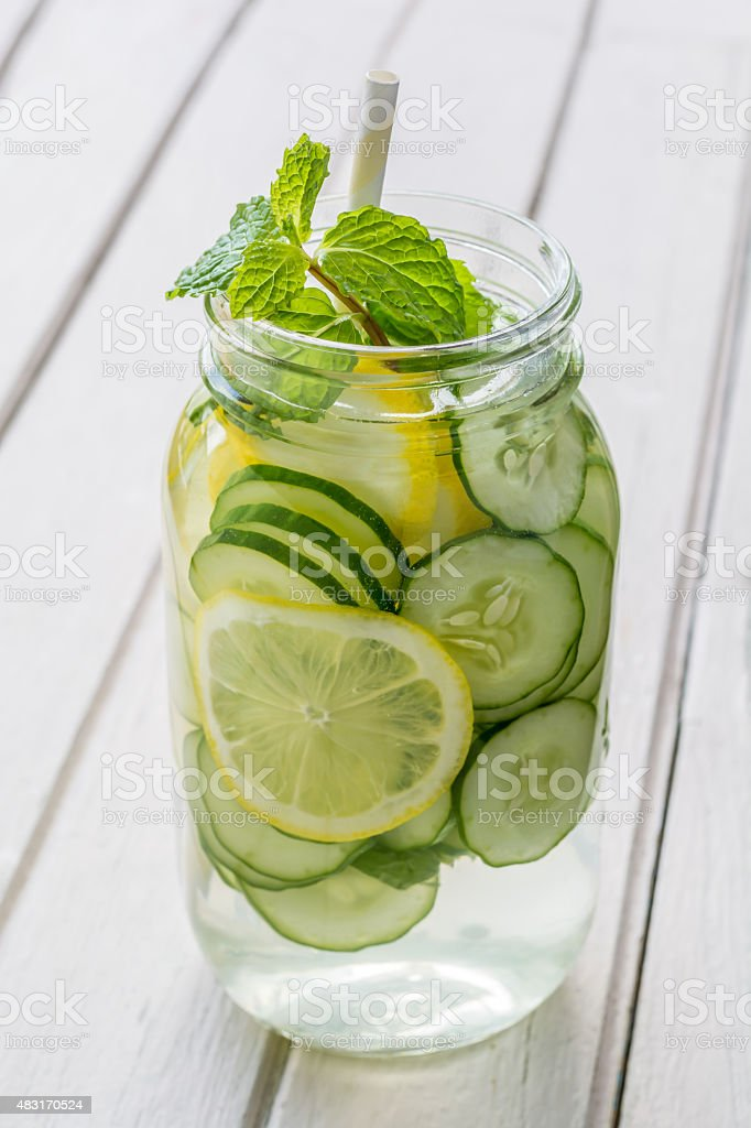 Infused water with lemon, cucumber and mint on wooden background stock photo