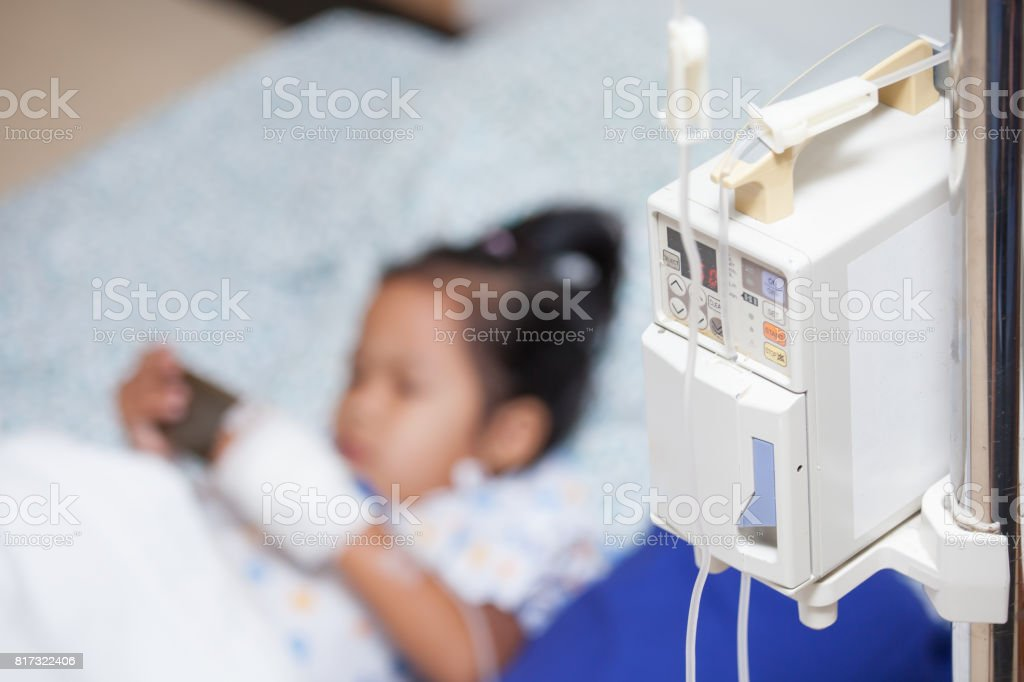 Infusion pump feeding IV drip into child patient in the hospital stock photo