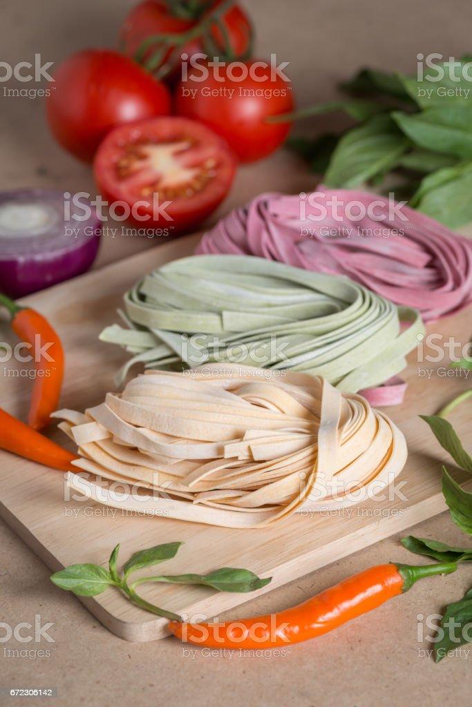 Ingredient made italian fettuccine pasta with basil, tomato, chili, onion. stock photo