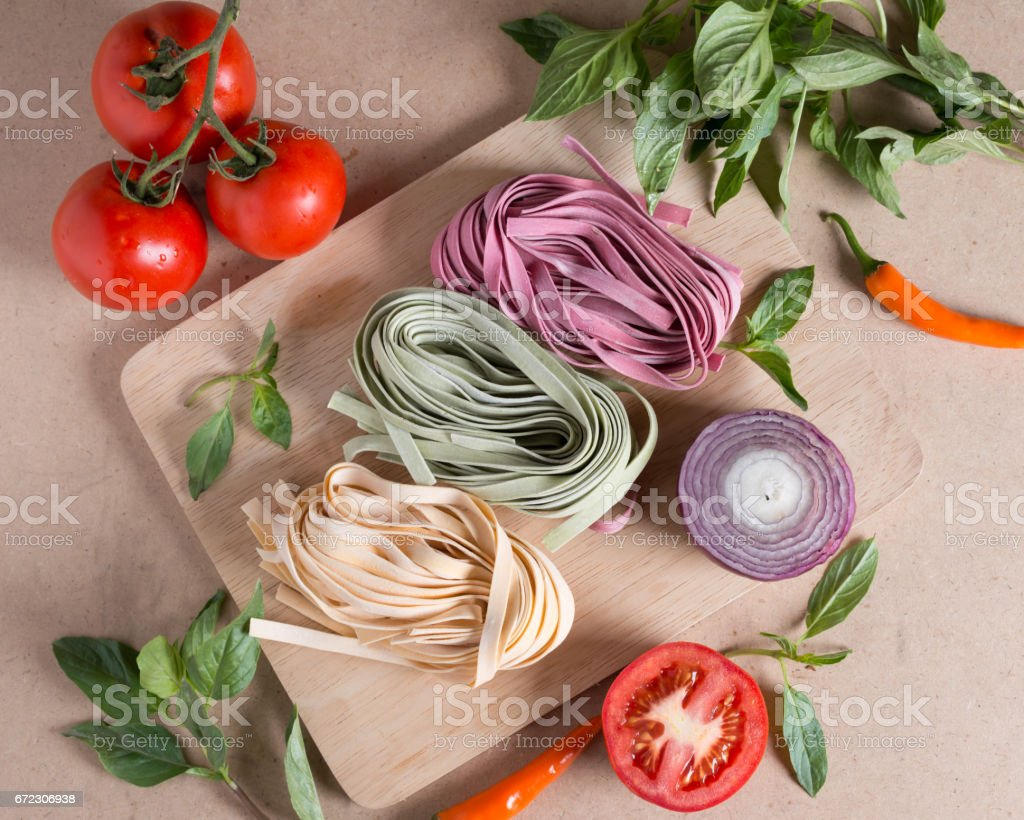 Ingredient made italian fettuccine pasta with basil, tomato, chili, onion. Top view. stock photo