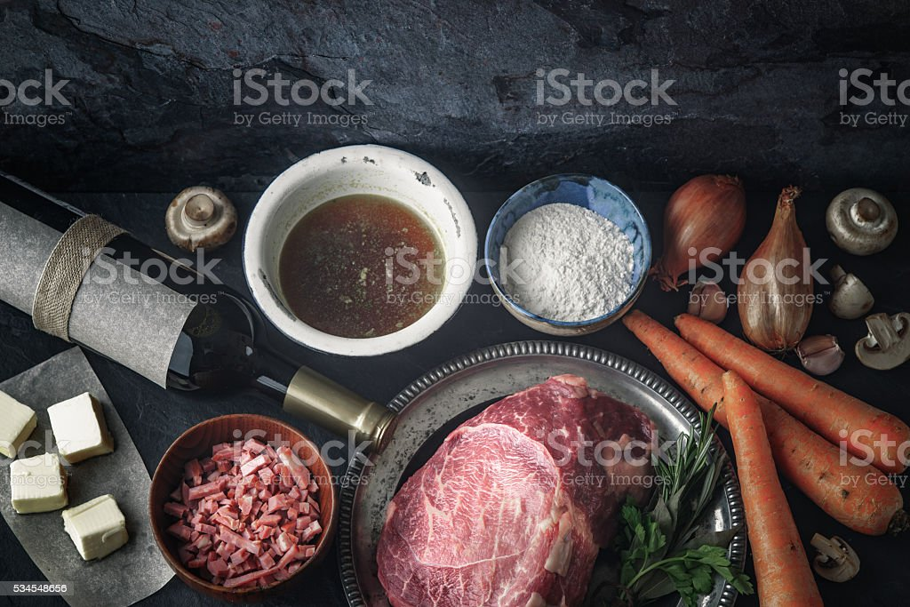 Ingredients for Boeuf Bourguignon on dark stone  table top view stock photo