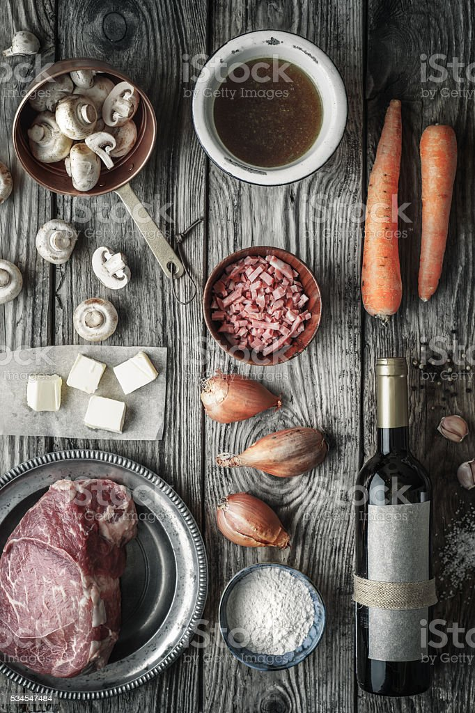 Ingredients for Boeuf Bourguignon on old wooden table top view stock photo