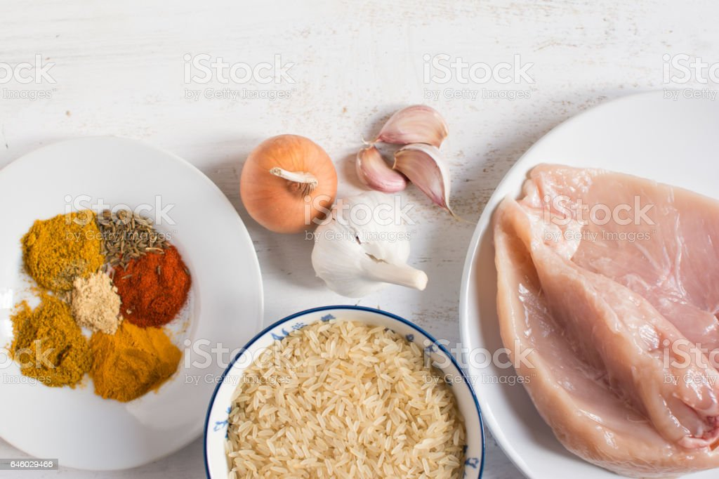 Ingredients for chicken curry: raw meat, uncooked rice, various spices, top view stock photo