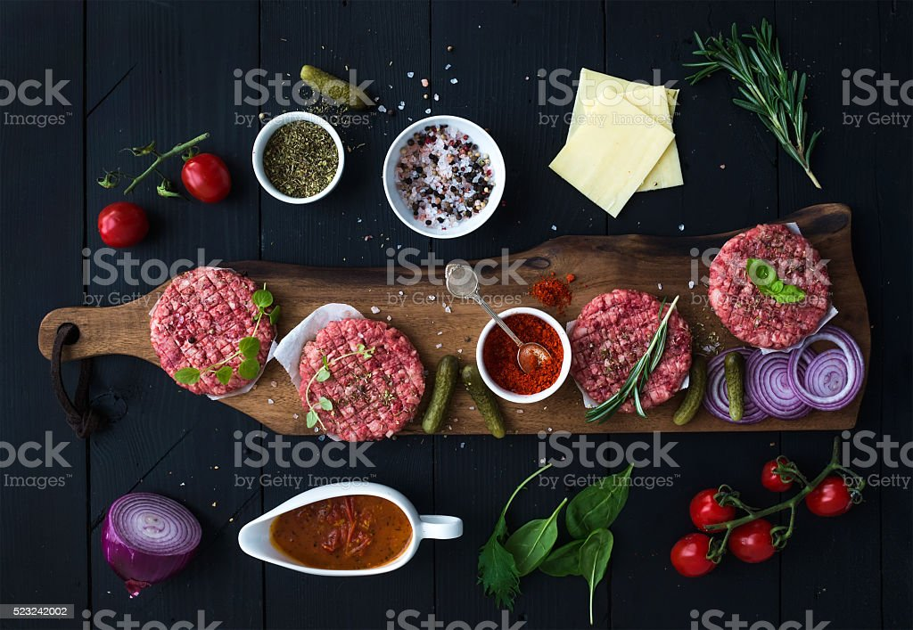 Ingredients for cooking burgers. Raw ground beef meat cutlets on stock photo