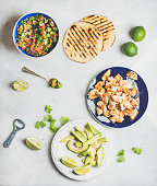Ingredients for cooking chicken and avocado tacos, grey marble background