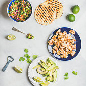 Ingredients for cooking chicken and avocado tacos over grey background