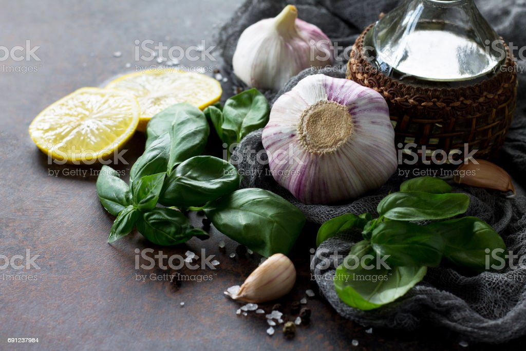 Ingredients for cooking - garlic, lemon, basil, spices and olive oil. Food background on the kitchen table. stock photo