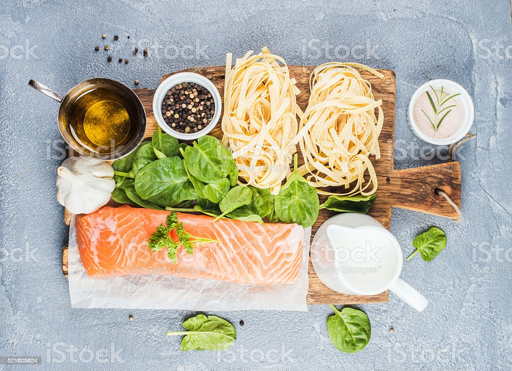 Ingredients for cooking pasta tagliatelle with salmon, spinach and cream stock photo